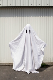 white ghost in front of a garage door