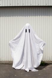 white ghost in front of a garage door
